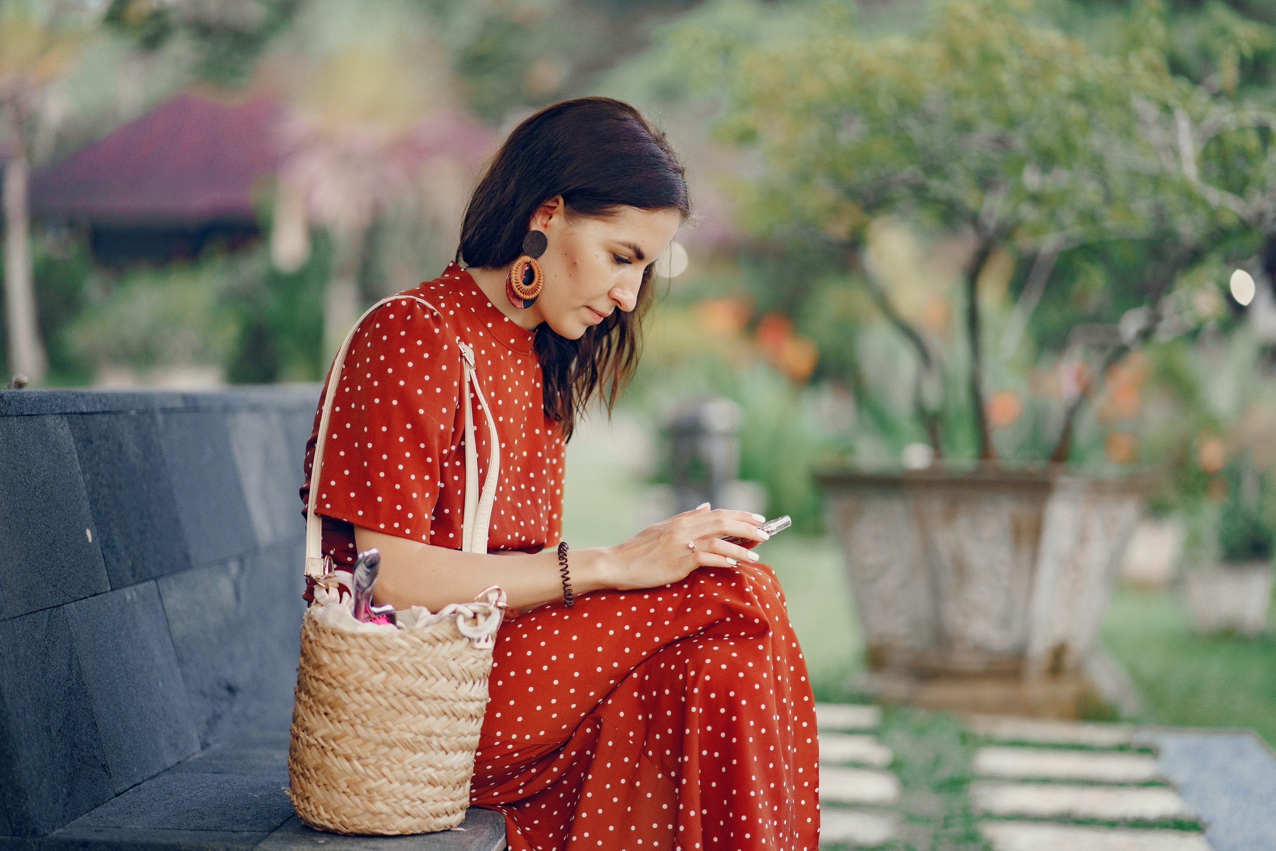 calm-woman-in-red-dress-using-smartphone-on-bench-4172870